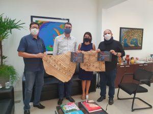 Pesquisadores do projeto e o reitor da UFMS, Marcelo Turine (à direita) entregam balanço das atividades executadas em 2020 ao secretário de Governo (ao centro).